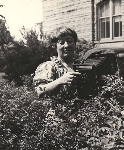 Black and white image of Ada Hayden with camera